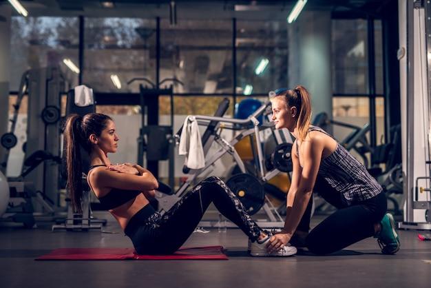 Zijaanzicht van jong gemotiveerd aantrekkelijk gezond sportief actief vormmeisje die abs oefeningen doen