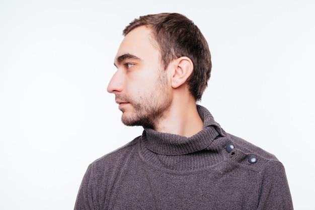 Zijaanzicht van jonge, bebaarde man geïsoleerd op grijze wall
