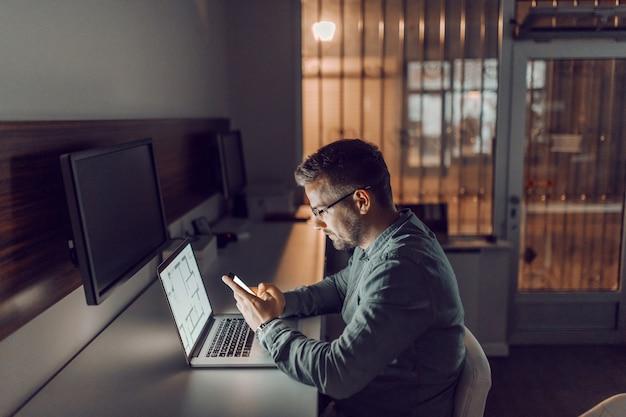 Zijaanzicht van jonge blanke hardwerkende architect met bril met behulp van slimme telefoon