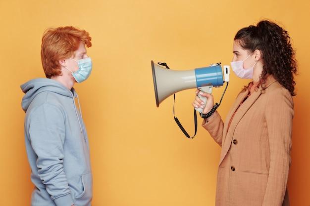 Zijaanzicht van jonge brunette vrouw in beschermend masker speaknig in megafoon terwijl staande voor man in blauwe hoodie