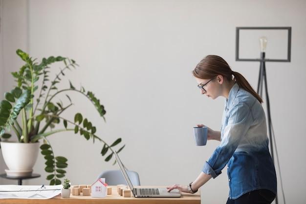 Zijaanzicht van jonge de koffiekop van de vrouwenholding terwijl het werken aan laptop op het werk