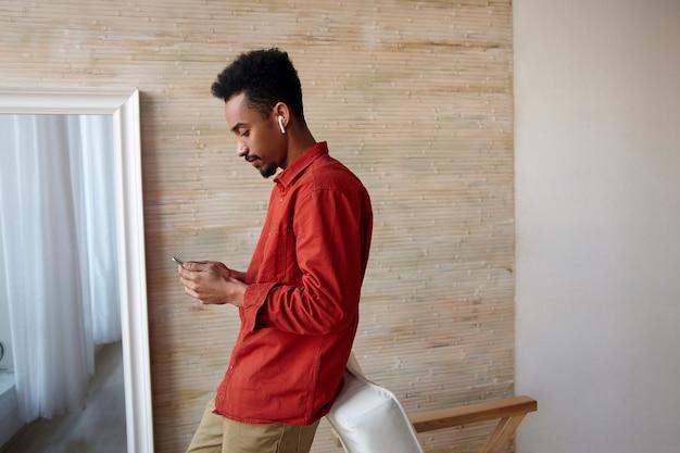 Zijaanzicht van jonge donkerhuidige brunette man met baard leunend op stoel tijdens het controleren van zijn sociale netwerken, staande op interieur in vrijetijdskleding