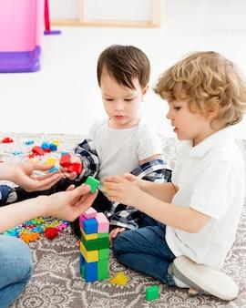 Zijaanzicht van jonge jongens die met speelgoed spelen