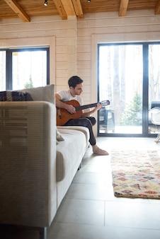 Zijaanzicht van jonge knappe de mensenzitting van de gitaarspeler op bank