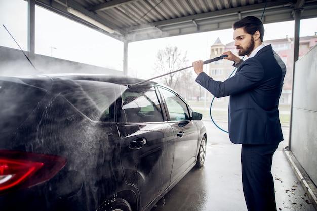 Zijaanzicht van jonge knappe ernstige modieuze gebaarde zakenman in het kostuum dat de auto met een waterkanon schoonmaakt in de handzelfbedieningswaspost.