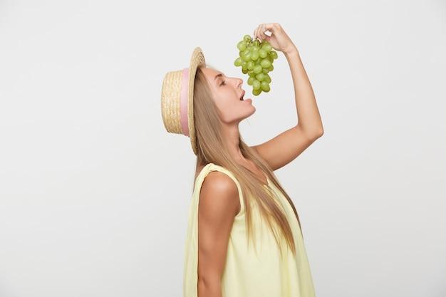 Zijaanzicht van jonge langharige blonde vrouw in boater hat hand opsteken met een tros druiven en gaan bijten, gekleed in een geel overhemd terwijl poseren op witte achtergrond