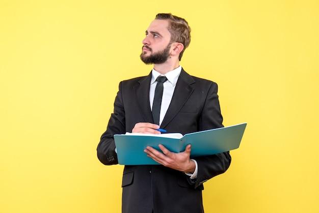 Zijaanzicht van jonge man zakenman opzoeken en denken terwijl pen naar de blauwe map op de gele muur wijst