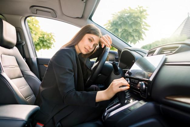 Zijaanzicht van jonge mooie bedrijfsdame in slimme vrijetijdskledingzitting in bestuurderszetel in haar auto.