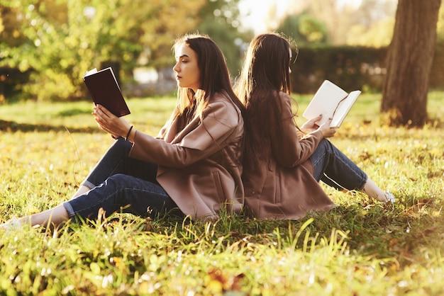 Zijaanzicht van jonge mooie brunette tweelingzusjes rug aan rug zitten op het gras met de benen licht gebogen in de knieën bruine boeken lezen en het dragen van casual jas in herfst zonnig park op onscherpe achtergrond