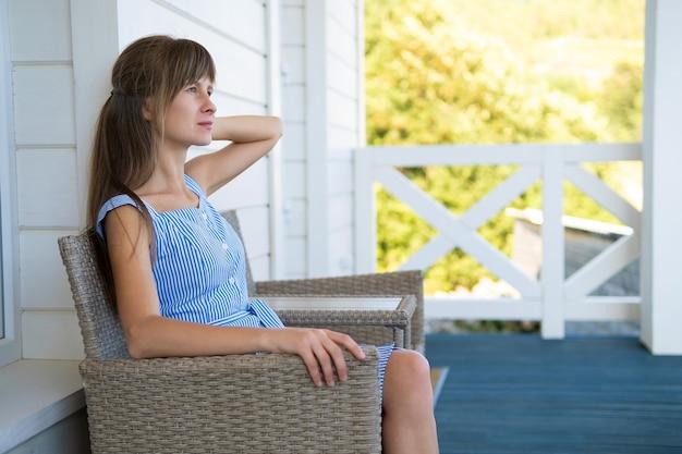 Zijaanzicht van jonge mooie vrouw rustend op frisse lucht zittend op de veranda thuis. concept van genieten van de natuur met goed weer.