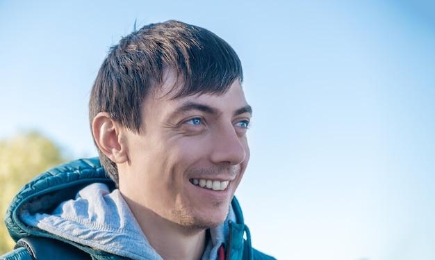 Zijaanzicht van jonge volwassen blanke donkerharige man lachend buitenshuis op een zonnige herfst of lentedag tegen blauwe hemel