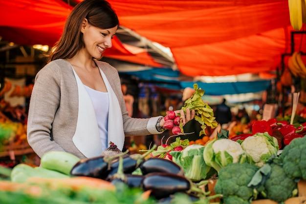 Zijaanzicht van jonge vrouw bij landbouwersmarkt, die groenten kiest.