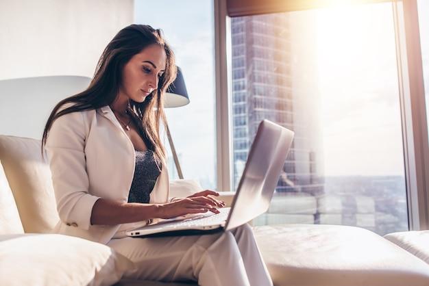 Zijaanzicht van jonge vrouw die op laptop werkt.