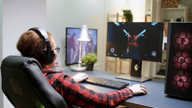 Zijaanzicht van jonge vrouw die schietspellen speelt die op een gamingstoel zitten. krachtige computeropstelling met draaiende neonventilatoren