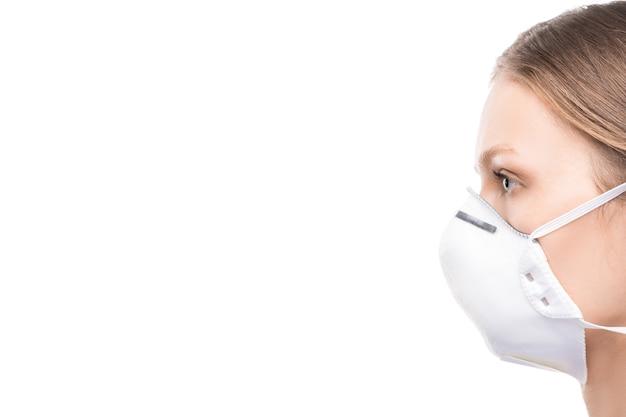 Zijaanzicht van jonge vrouw in beschermend masker die geïsoleerd staan tijdens de periode van gevaarlijke virusverspreiding over de hele wereld