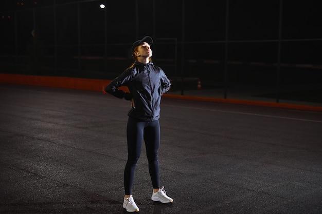 Zijaanzicht van jonge vrouw in sportieve kleding en pet wandelen met rust buiten een pauze nemen bij ni...