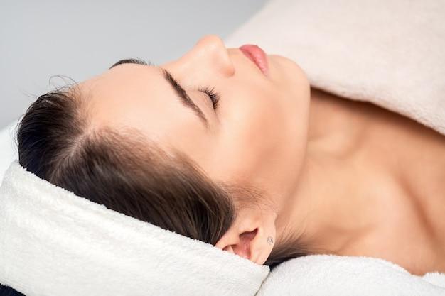 Zijaanzicht van jonge vrouw liggend op de tafel van de schoonheidsspecialiste met gesloten ogen tijdens het wachten op cosmetische procedure in de schoonheidssalon