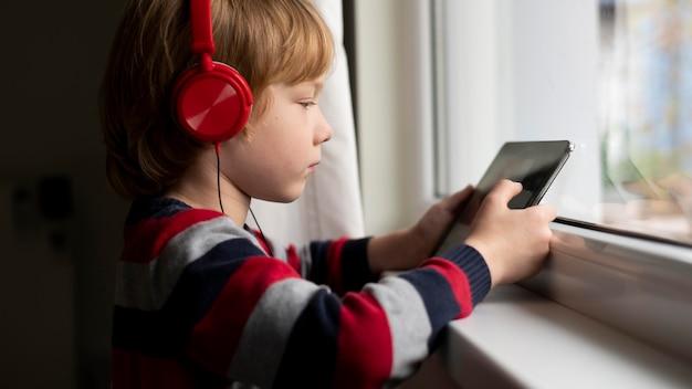 Zijaanzicht van jongen die tablet met hoofdtelefoons gebruikt