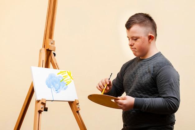 Zijaanzicht van jongen met het syndroom van down schilderen