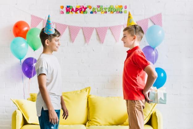 Zijaanzicht van jongens verbergende gift van zijn vriend thuis Gratis Foto