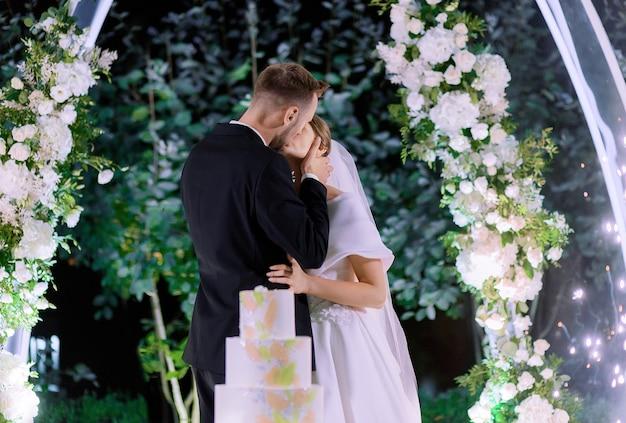 Zijaanzicht van jonggehuwden die kussen tijdens het huwelijksfeest op een achtergrond van decor met bloemen