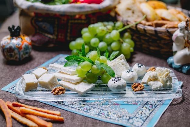 Zijaanzicht van kaasplaat met druiven en walnoten