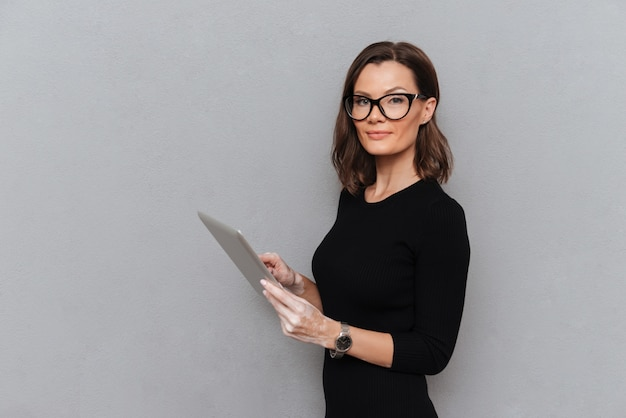 Zijaanzicht van kalme bedrijfsvrouw die tabletcomputer met behulp van