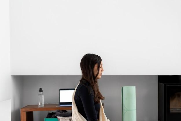 Zijaanzicht van kalme jonge vrouw met gesloten ogen beoefenen van mindfulness en mediteren tijdens yoga beoefening thuis