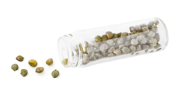Zijaanzicht van kappertjes in transparante glazen fles. voedselingrediënt geïsoleerd op een witte achtergrond