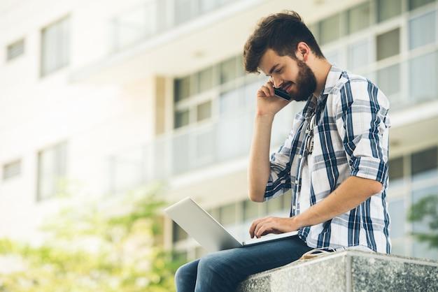Zijaanzicht van kerel in vrijetijdskleding die telefoongesprek beantwoorden terwijl in openlucht gegevensverwerking op laptop