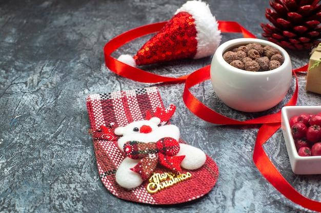 Zijaanzicht van kerstman hoed en cornel chocolade nieuwjaarssok rode conifeer kegel cadeau op donkere ondergrond