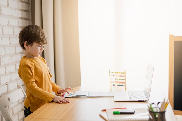Zijaanzicht van kind dat thuis bij bureau bestudeert