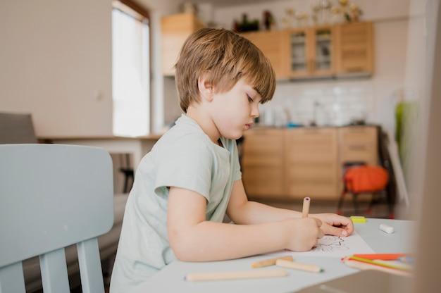 Zijaanzicht van kind dat thuis leert