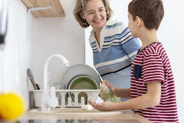 Zijaanzicht van kind dat zijn handen wast terwijl het spreken aan zijn moeder