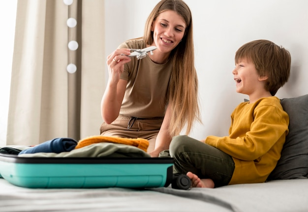 Zijaanzicht van kind en moeder die thuis met vliegtuigbeeldje spelen