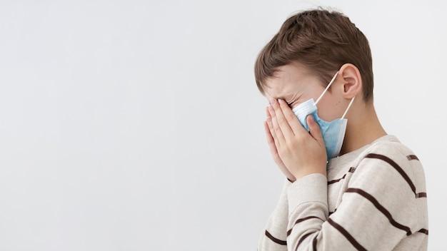 Zijaanzicht van kind met medisch masker dat zijn gezicht behandelt