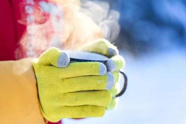 Zijaanzicht van kinderen hand in gele handschoenen met warme kop chocolade of cacao in winterbos. detailopname.