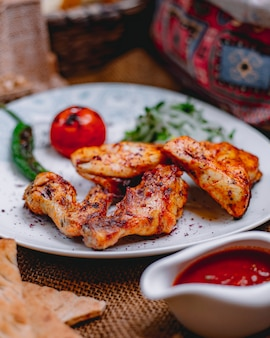 Zijaanzicht van kip kebab met gegrilde groenten en pittige tomatensaus op tafel