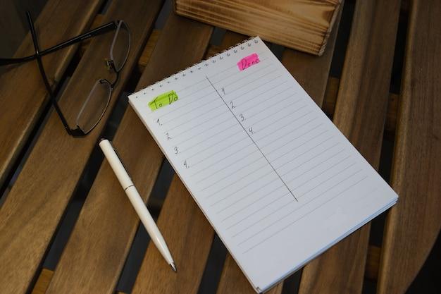 Zijaanzicht van kladblok met gedaan lijst, glazen op houten tafel, doelen concept