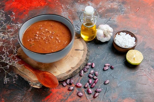 Zijaanzicht van klassieke tomatensoep in een blauwe komlepel op houten het knoflookzout en de citroen van de dienbladoliefles op gemengde kleurentafel