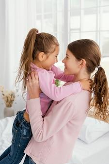 Zijaanzicht van kleine zusjes samen thuis