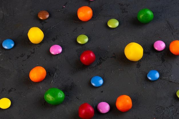 Zijaanzicht van kleurrijk suikergoed dat op zwarte wordt verspreid