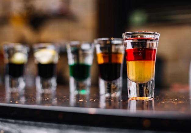 Zijaanzicht van kleurrijke cocktails in borrelglaasjes op een bar staan