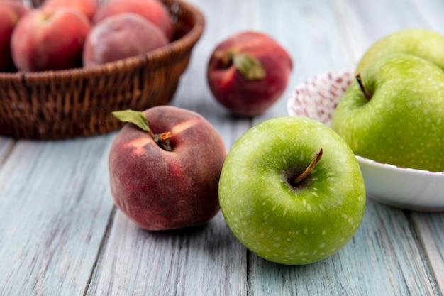 Zijaanzicht van kleurrijke en vers fruit zoals perziken op een emmer en appel op een witte kom op grijze houten oppervlak