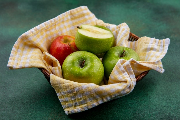 Zijaanzicht van kleurrijke en verse appels op een emmer versierd met een gecontroleerd tafelkleed op groene ondergrond