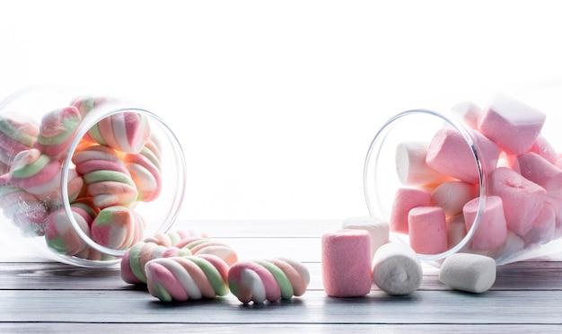 Zijaanzicht van kleurrijke gedraaide marshmallow verspreid uit een glazen pot op wit