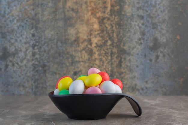 Zijaanzicht van kleurrijke ronde snoepjes in zwarte kom over grijze achtergrond.