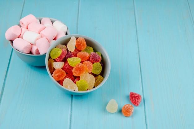Zijaanzicht van kleurrijke smakelijke marmelade snoepjes en marshmallows in kommen op blauw