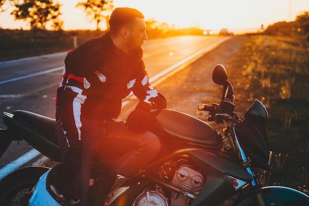 Zijaanzicht van knappe bebaarde man in beschermende uitrusting zittend op staande op de motorstoel langs de weg met helm in de hand op onscherpe achtergrondverlichting achtergrond van landroute