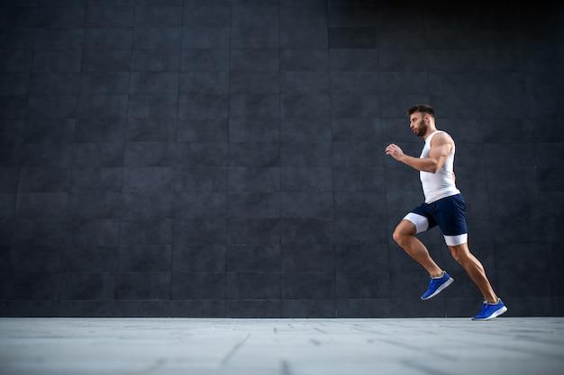 Zijaanzicht van knappe kaukasische gespierde fit man loopt snel buitenshuis. in de achtergrond is grijze muur.